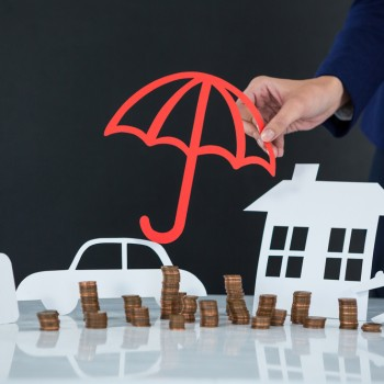 Conceptual image of businesswoman protecting her wealth with umbrella
