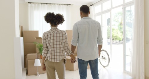 Loving young couple saying goodbye to their home as they prepare to move standing hand in hand surveying the pile of packed boxes