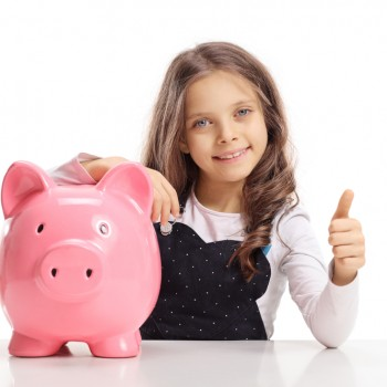 Little girl with a piggybank sitting at a table and making a thu