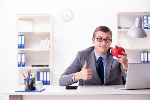 Young employee with piggybank in pension savings concept