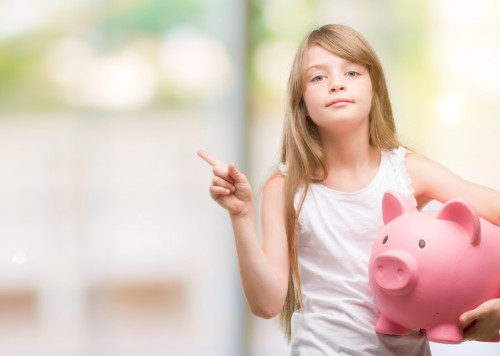 Young blonde toddler holding piggy bank very happy pointing with hand and finger to the side