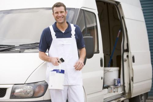 Painter standing with van smiling