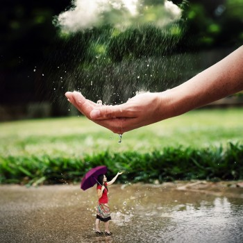 a-woman-in-a-rain-shower-is-being-protected-by-a-large-hand_BQg6XJGlC