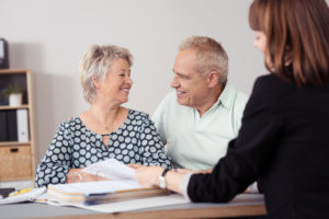 Happy Senior Couple Talking to a Female Agent About downsizing home